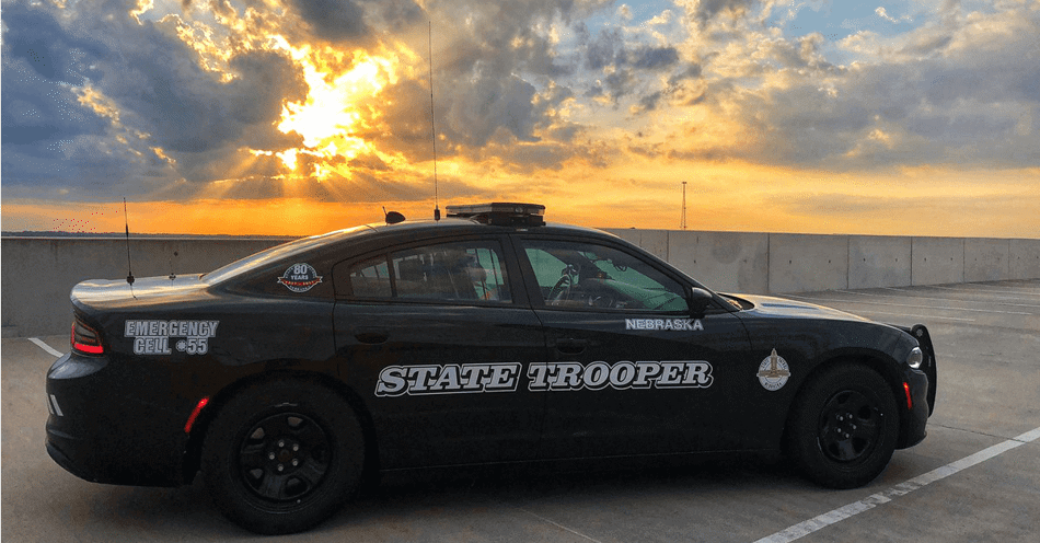 Passenger side of a Nebraska State Patrol Cruiser with a sun set in the background.